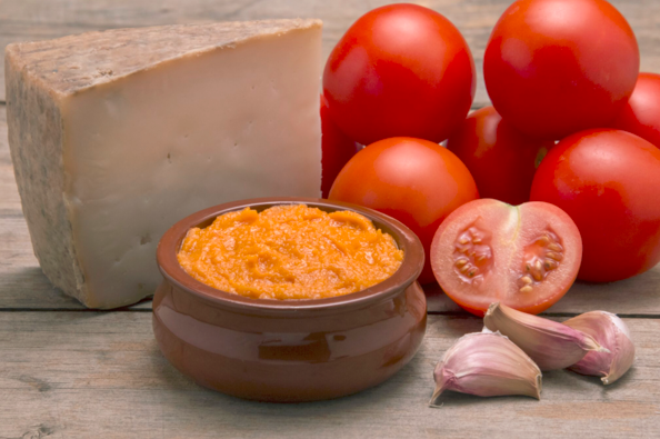 image of hard cheese and cheest dip with tomatos and garlic cloves